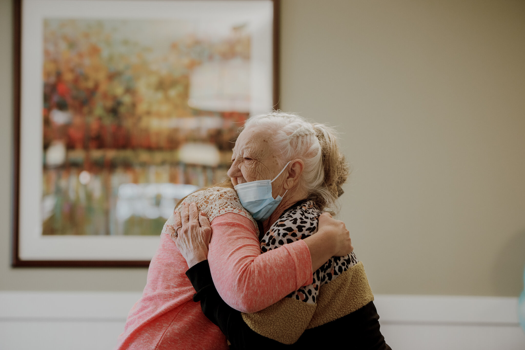 Two people embrace at a nursing home; one woman wears her mask below her nose