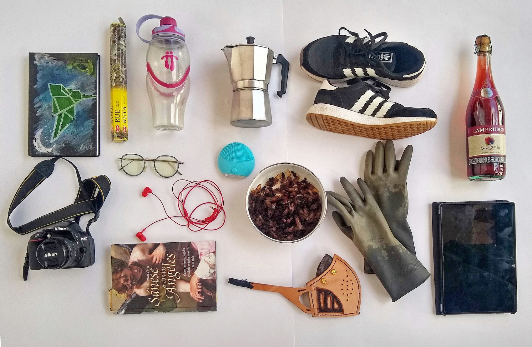 Items laid out on a floor, including a water bottle, coffee-maker, camera, shoes, and gloves