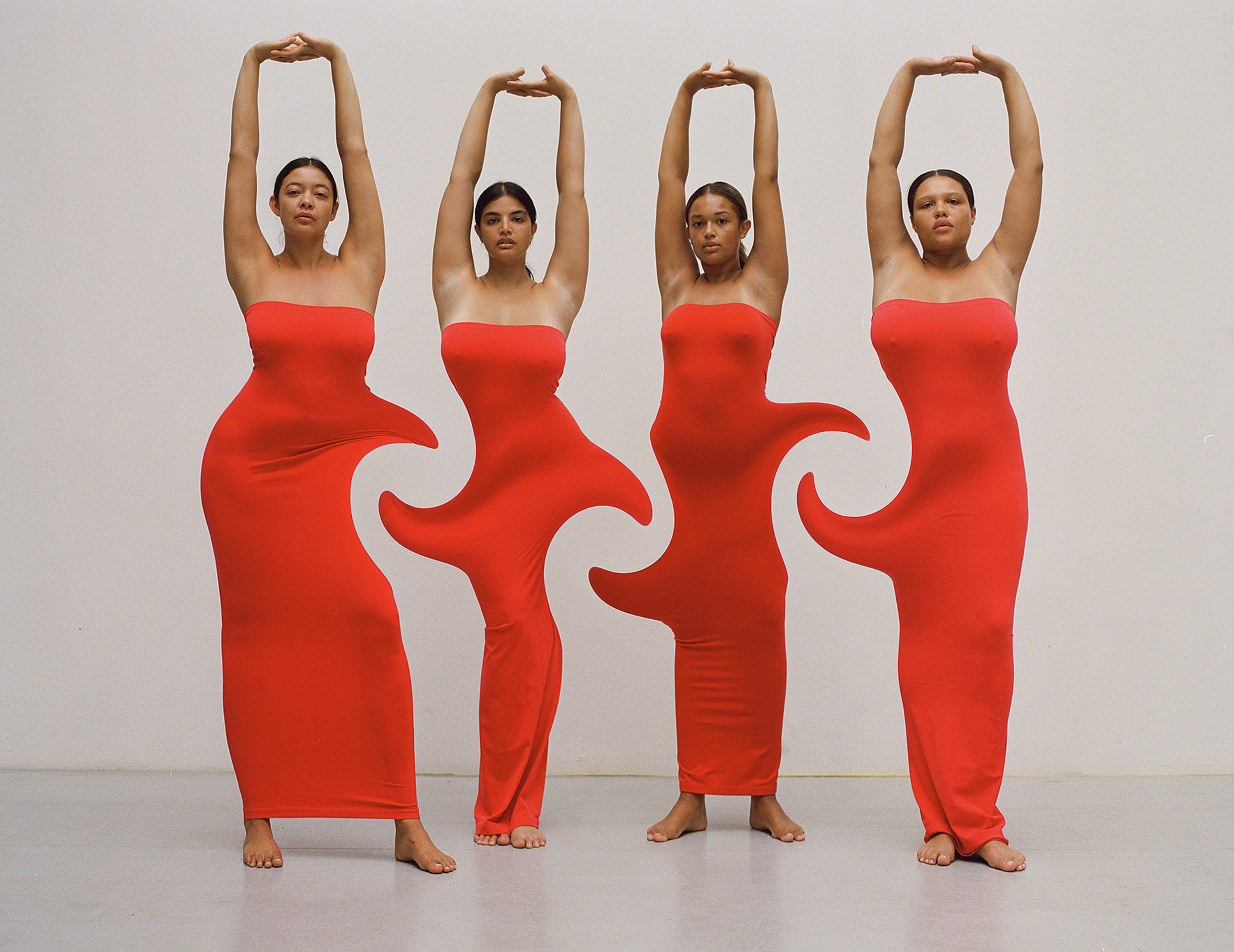 Four women with their arms raised in red dresses which are digitially manipualted to swirl together