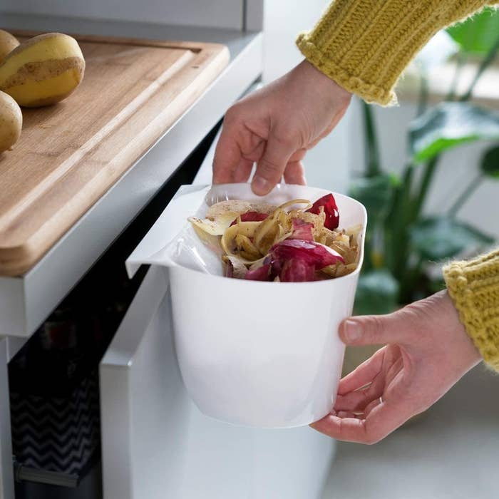 A person holding a bin of food scraps over a cabinet door next to a cutting board