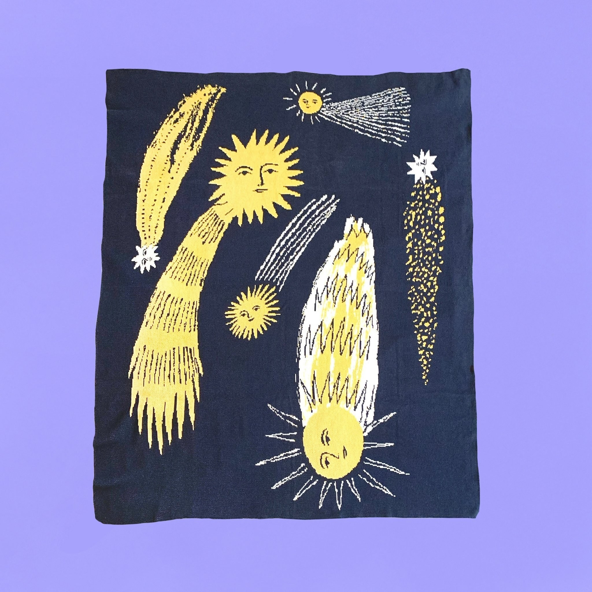 A throw blanket in dark blue with yellow and white illustrated comets, each with a face, flying through the sky