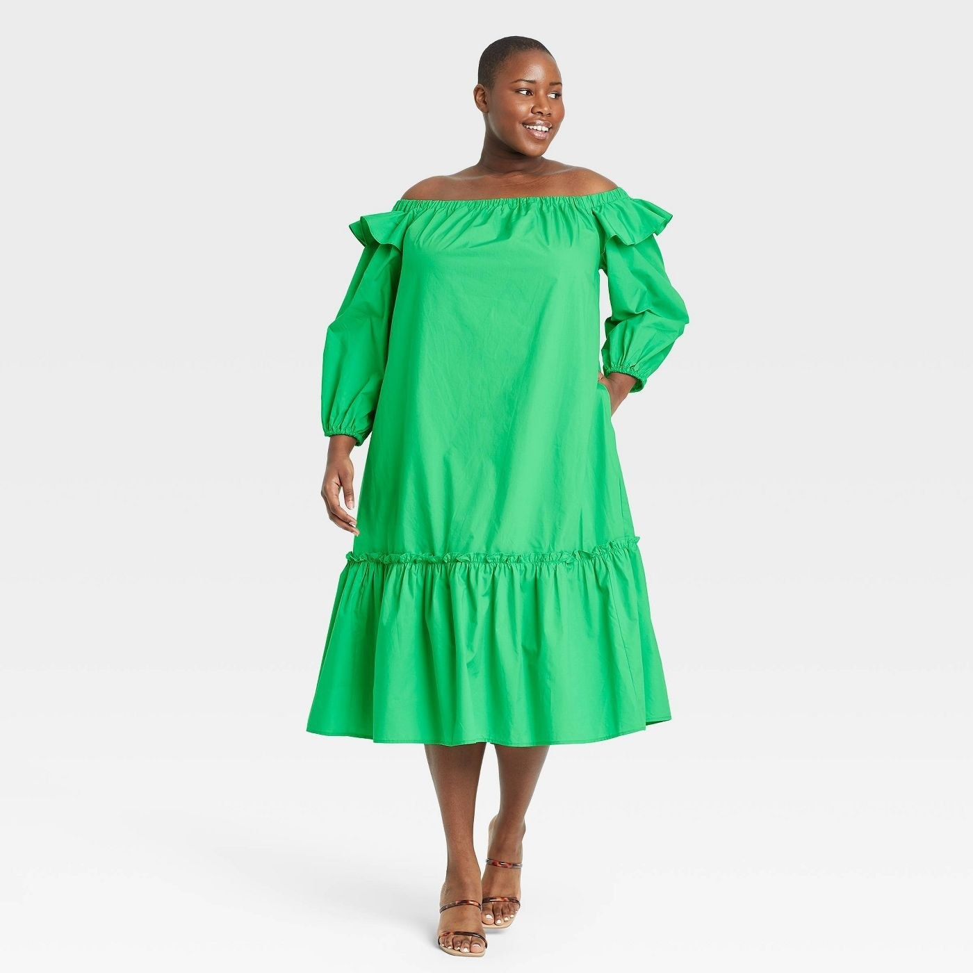 Model wearing green dress with tiered skirt, goes past the knee