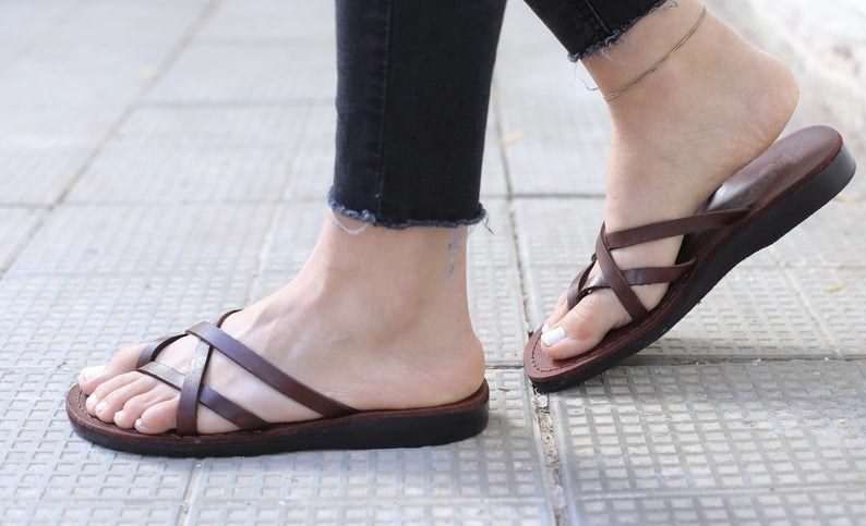 a model wearing the brown sandals with four toe straps