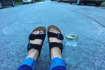 a reviewer wearing the sandals in black and sitting in the street