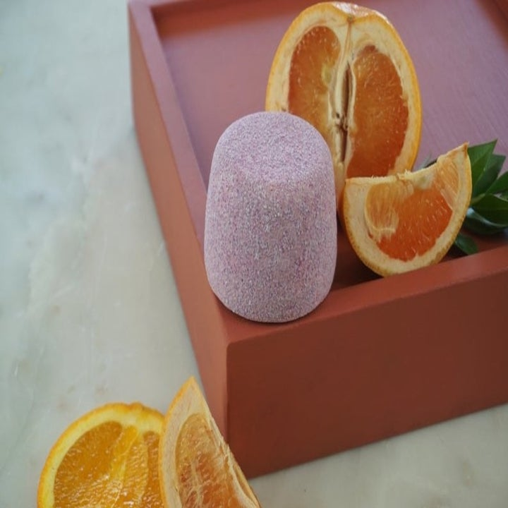 MuttCosmetics bath bomb placed on tray next to fruit slices