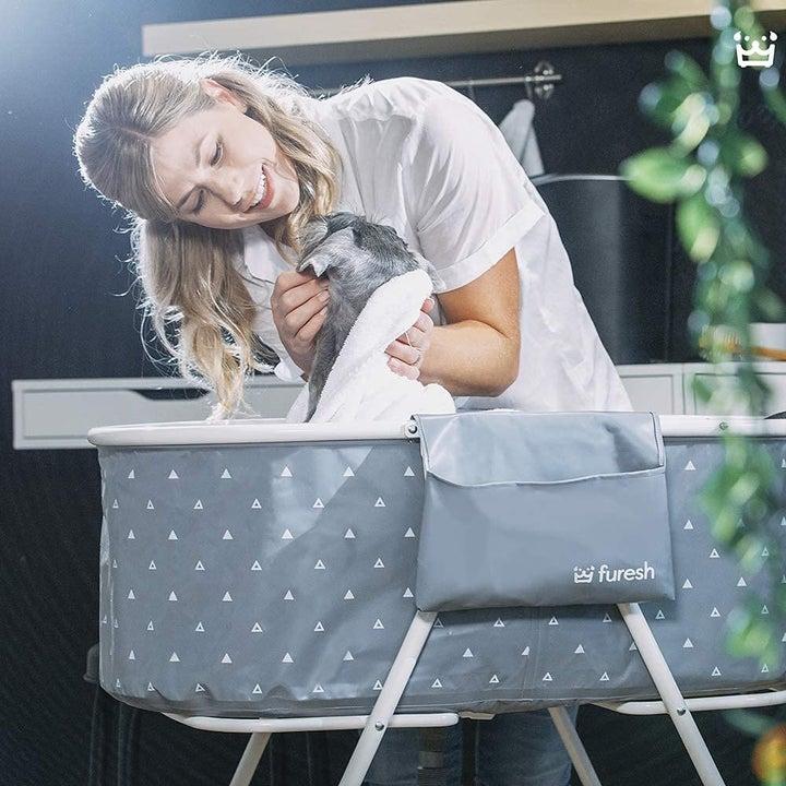 Model drying off dog in foldable dog bath