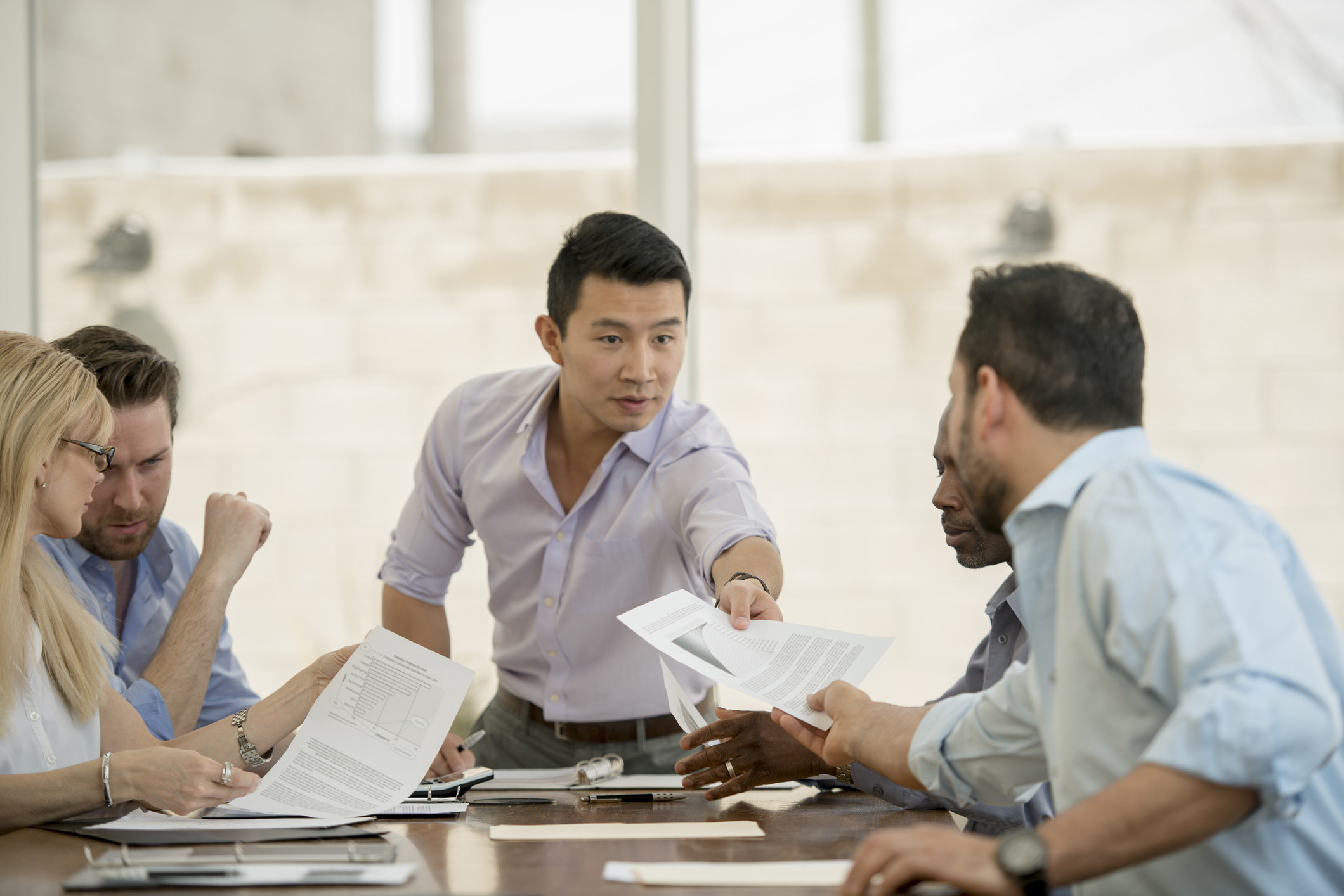Simu Liu having a discussion about financial data with a multi-ethnic group of business professionals during a boardroom meeting at the office.