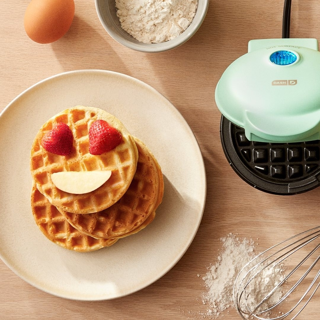 Two waffles on a plate next to the waffle maker