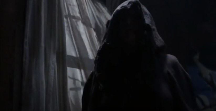 A black-hooded figure by white curtains