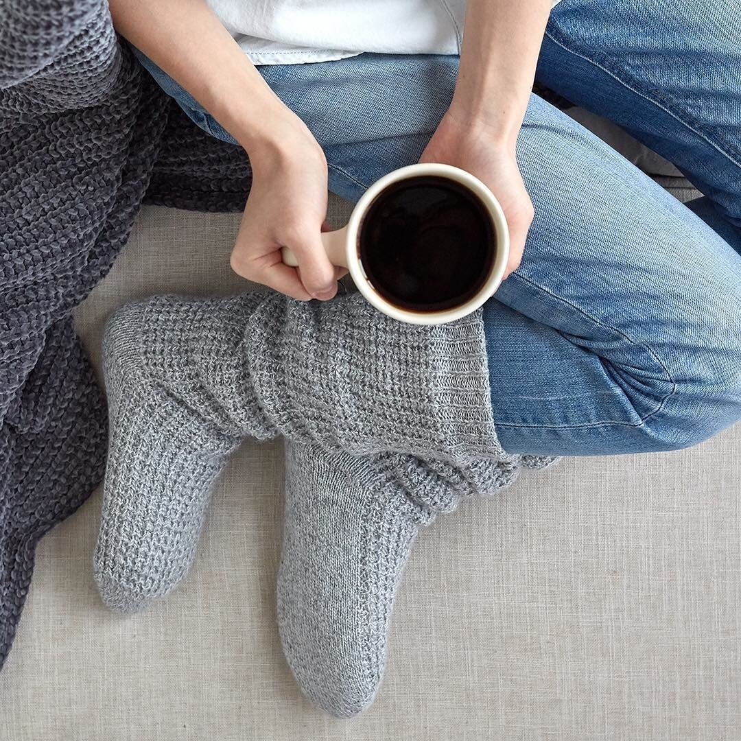 A person wearing the socks while holding a cup of coffee