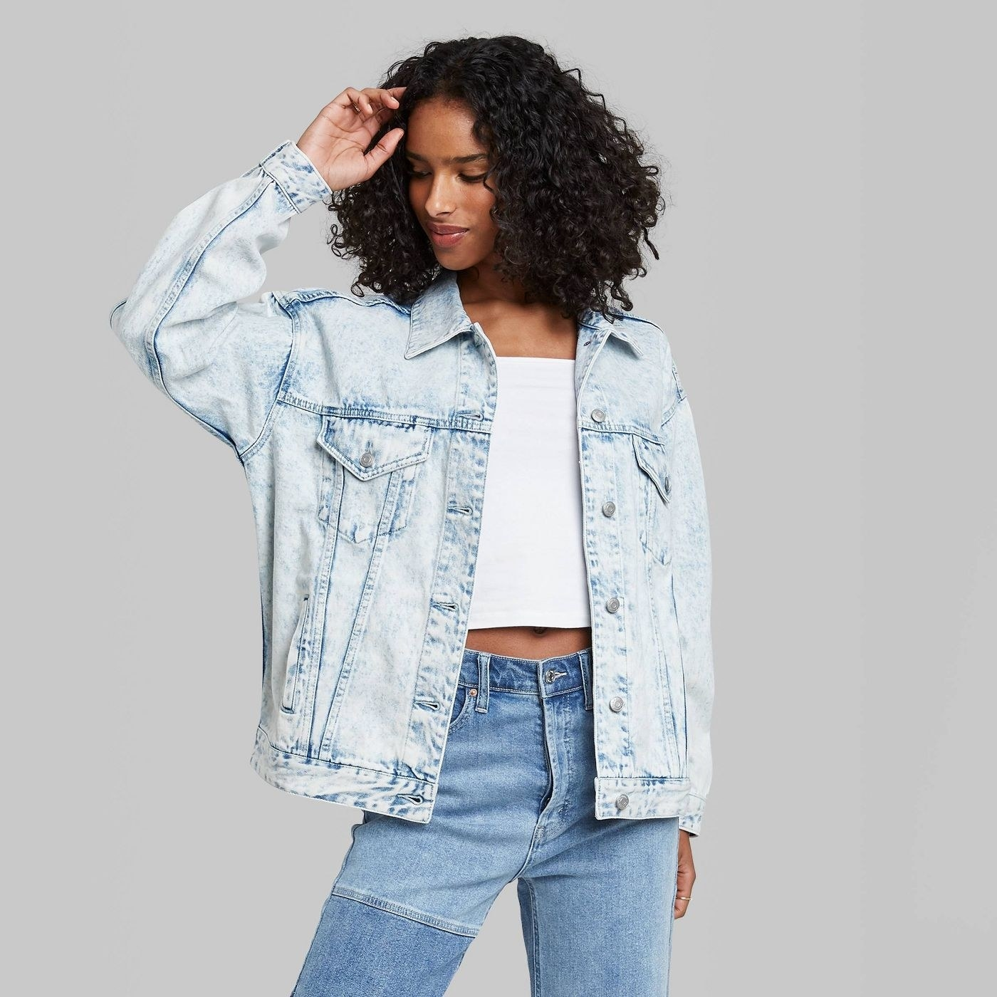 Model wearing light wash jean jacket with pockets on the bust area