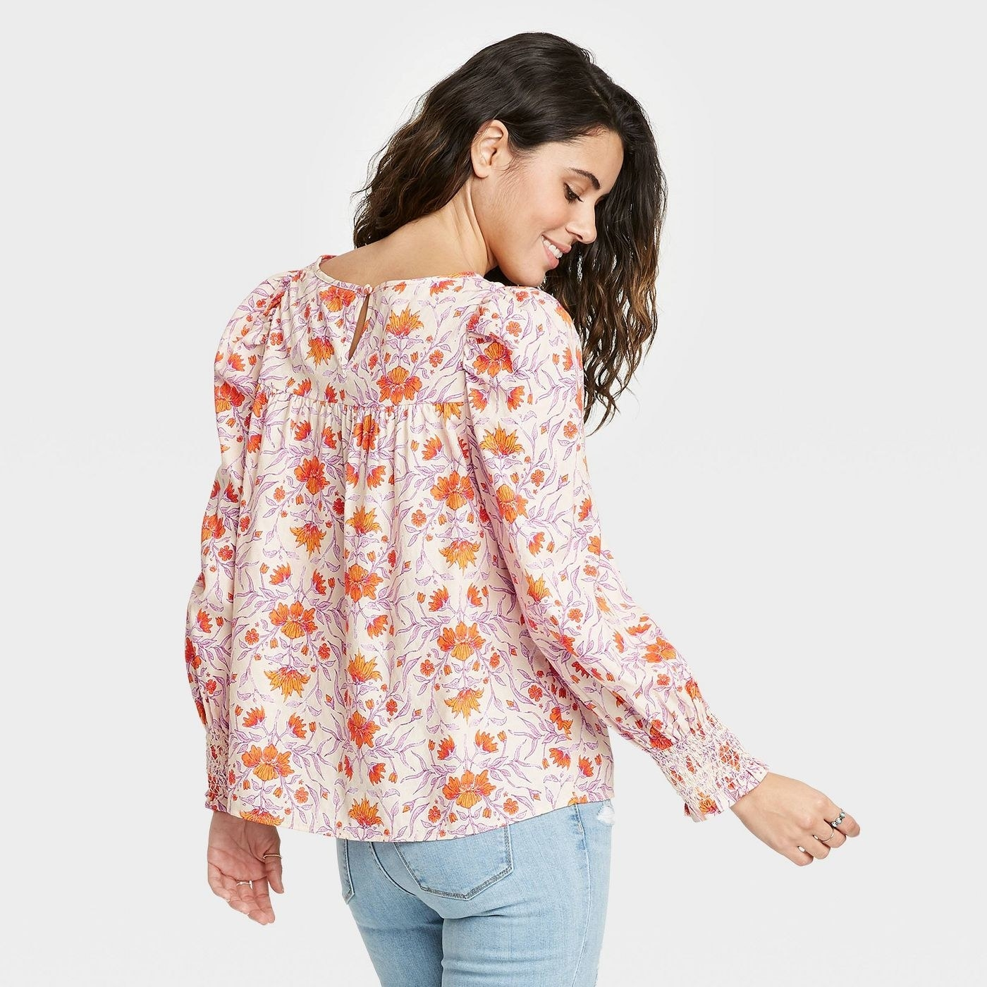 Model wearing white blouse with orange floral print, and lilac pattern