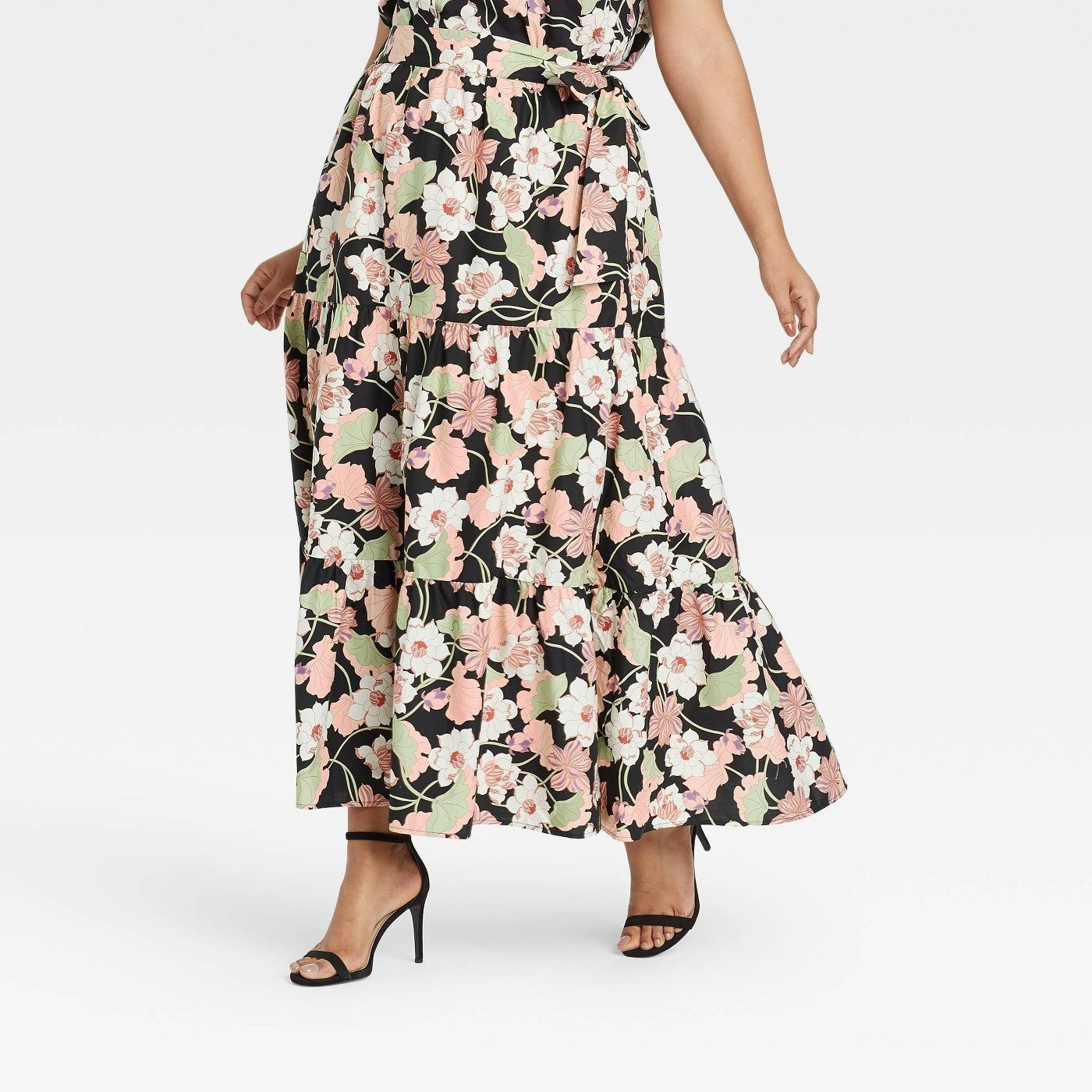 Model wearing black skirt with a green, white, and light pink floral pattern