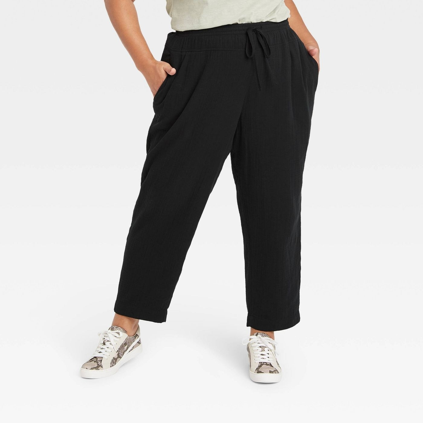 Model wearing black pants with elastic band, stops at the ankles
