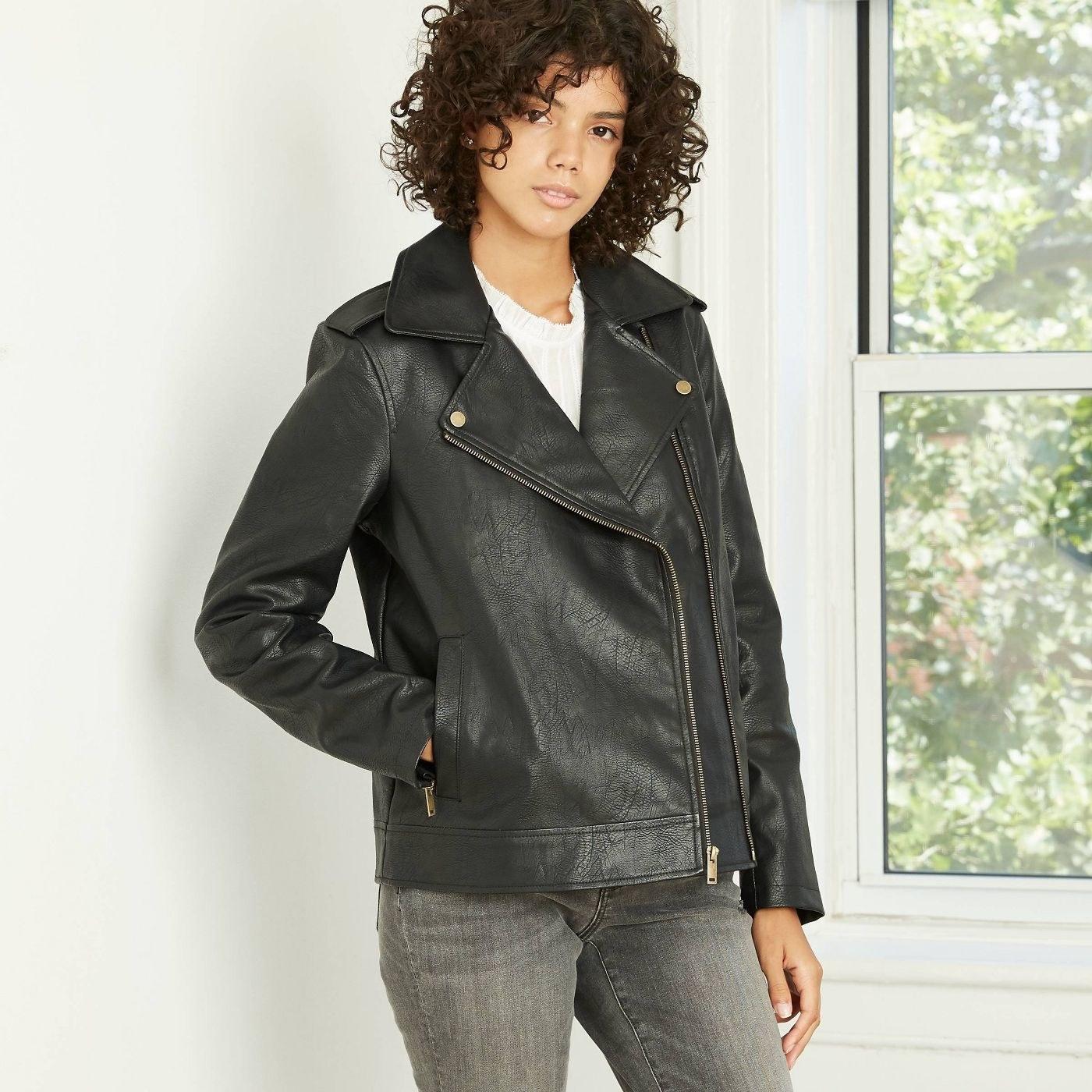 Model wearing black leather jacket with side gold zipper