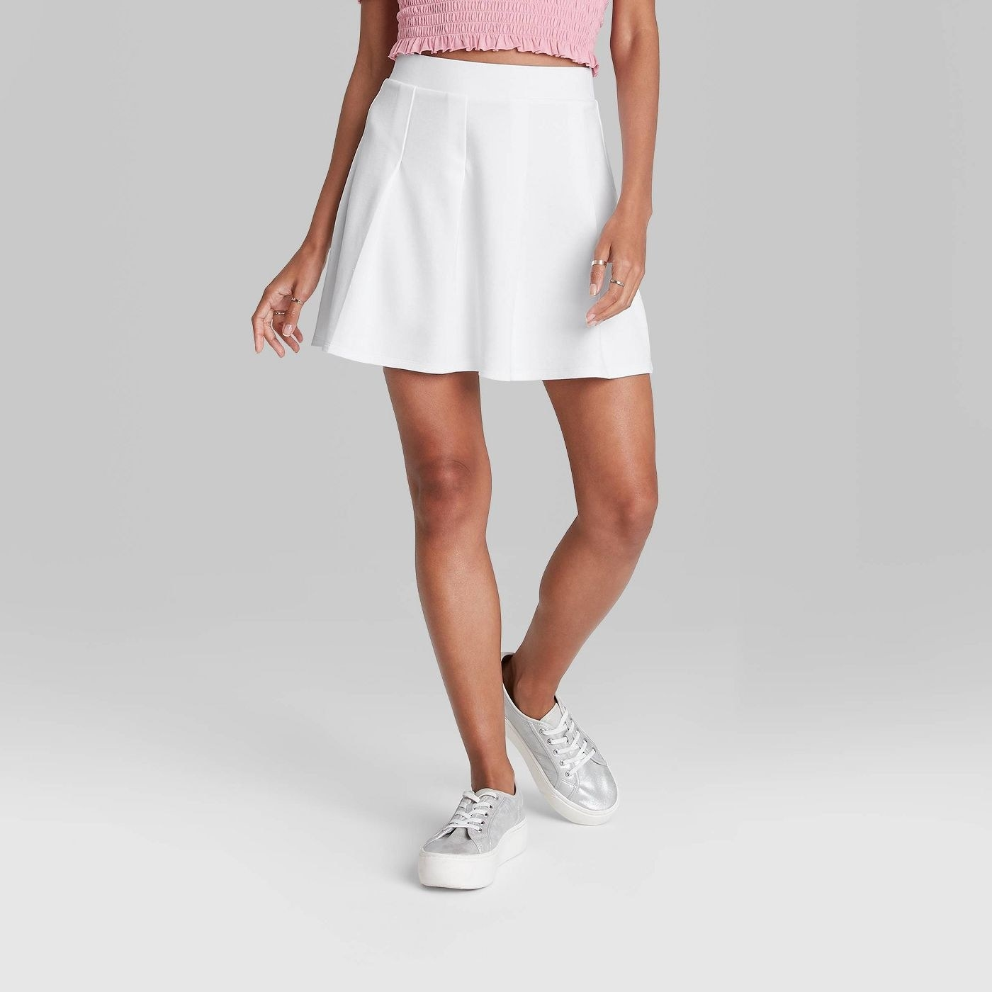 Model wearing white shirt with three pleats at the top