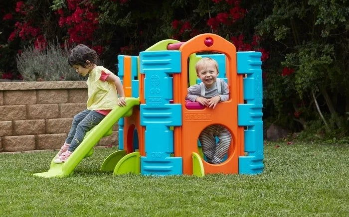 Two kids using the activity park playhouse outside