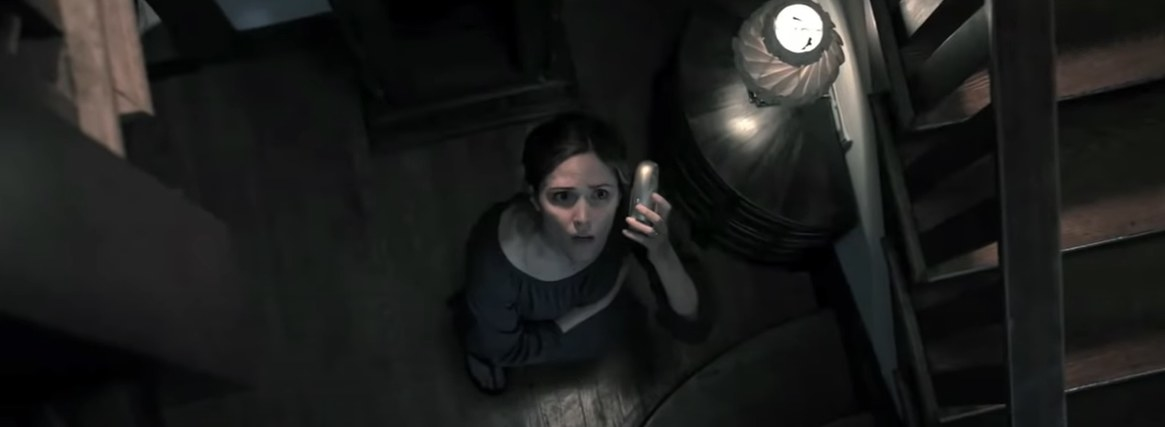 Woman listening to a baby monitor while looking upstairs