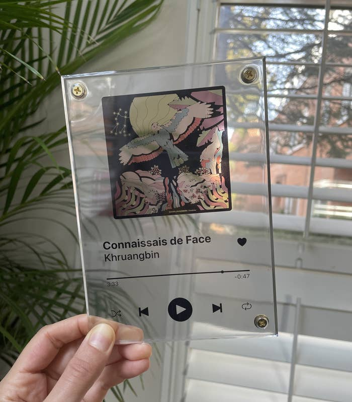 Brittany holding up a song plaque with Khruangbin's album Mordechai on it, showing the song Connaissais de Face
