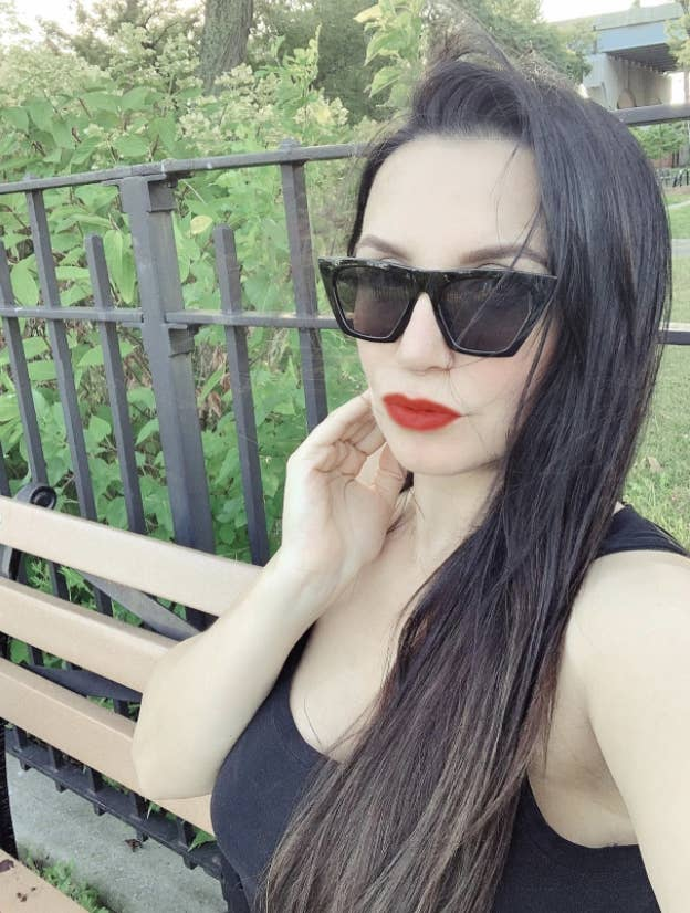 reviewer with dark hair and red lips wearing the sunglasses with a cat eye and pointed outer corners