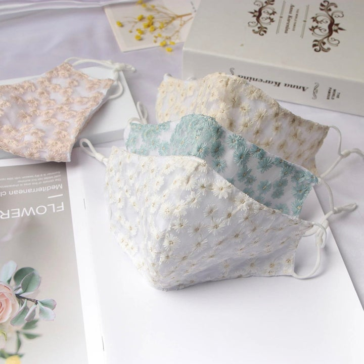White masks with floral embroidery in blue, yellow, white, and pink