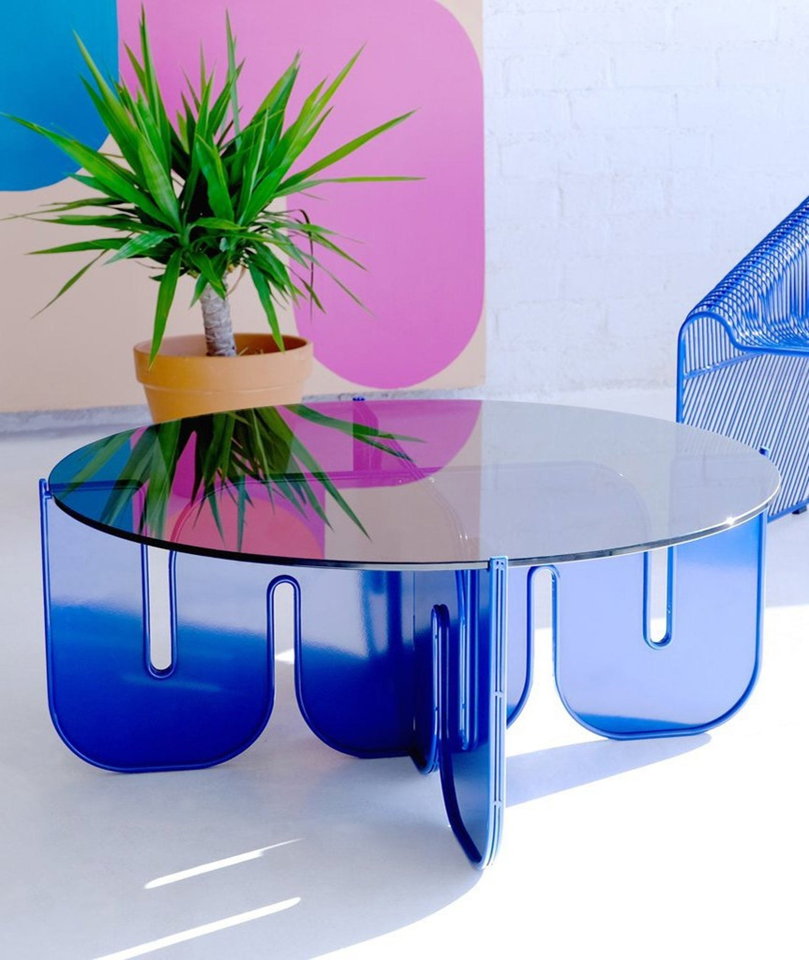 a blue lucite coffee table with wavy legs