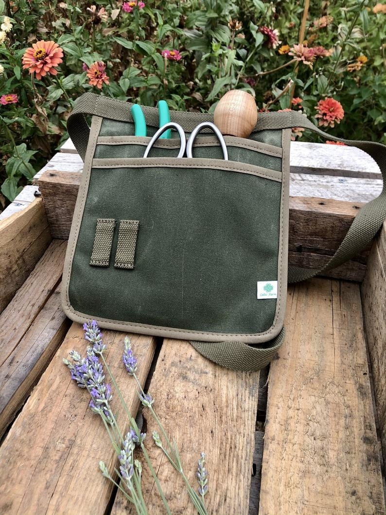 Green belted pouch with two deep pockets full of gardening tools