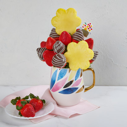 a chocolate-covered strawberry and pineapple fruit arrangement in a mug