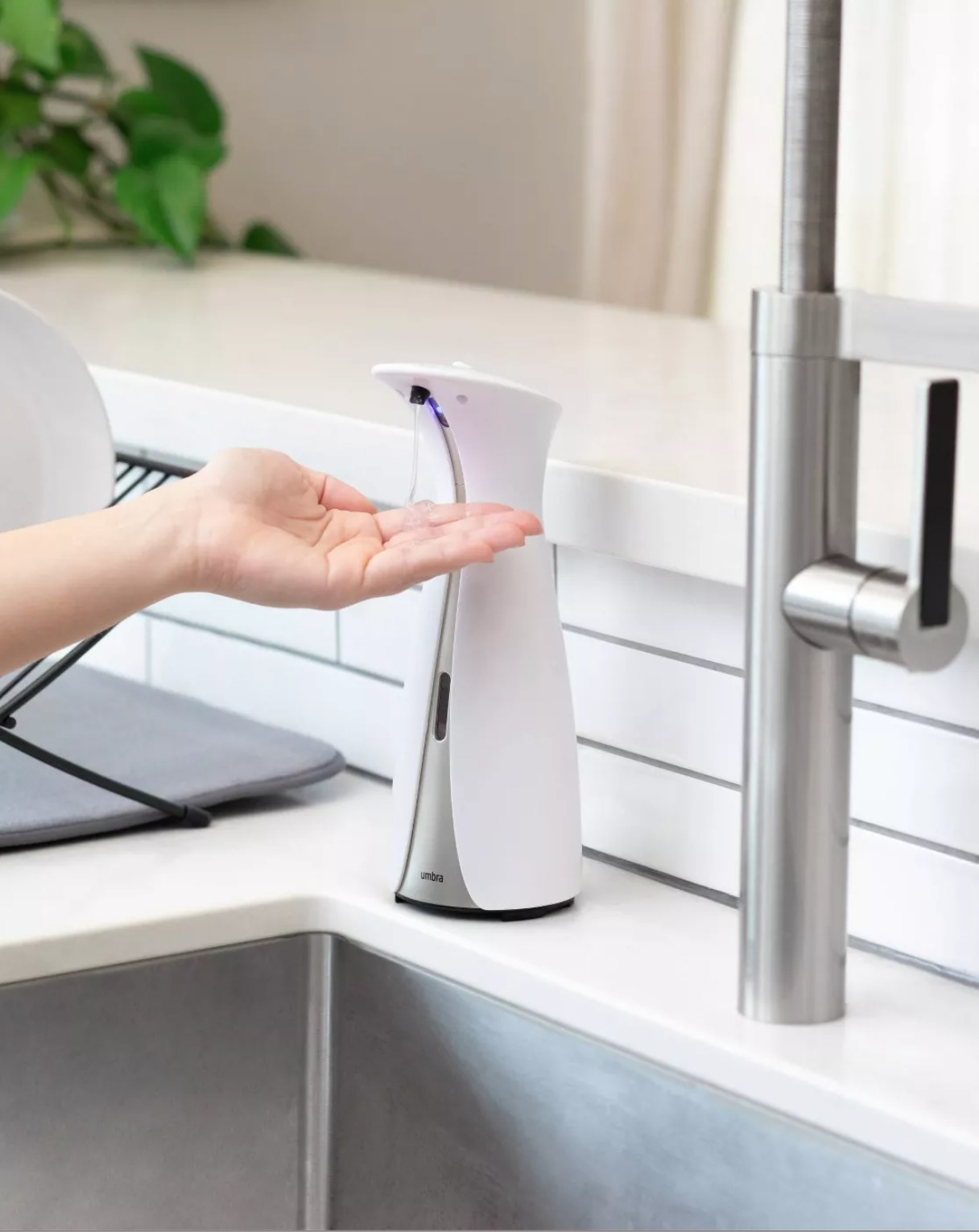 The soap dispenser releasing soap onto a hand