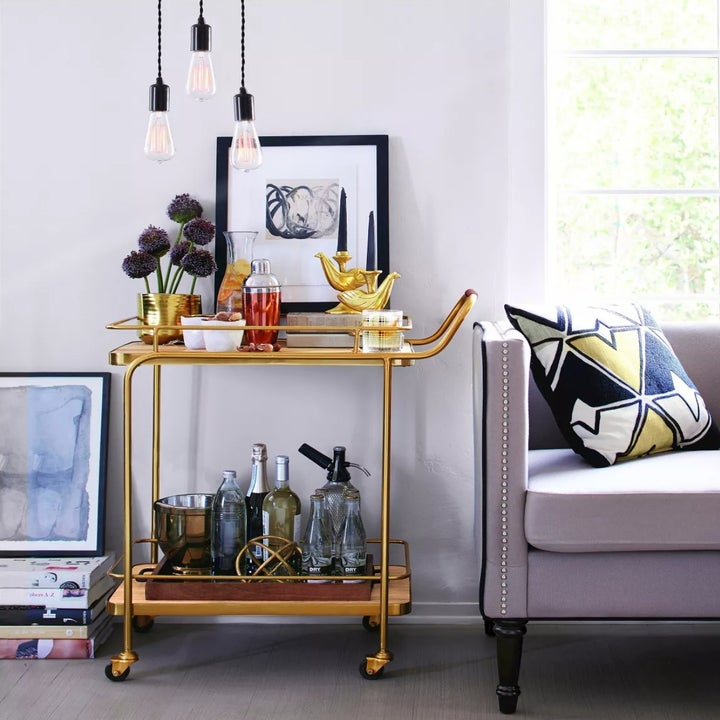 The gold bar cart holding drinks and glasses