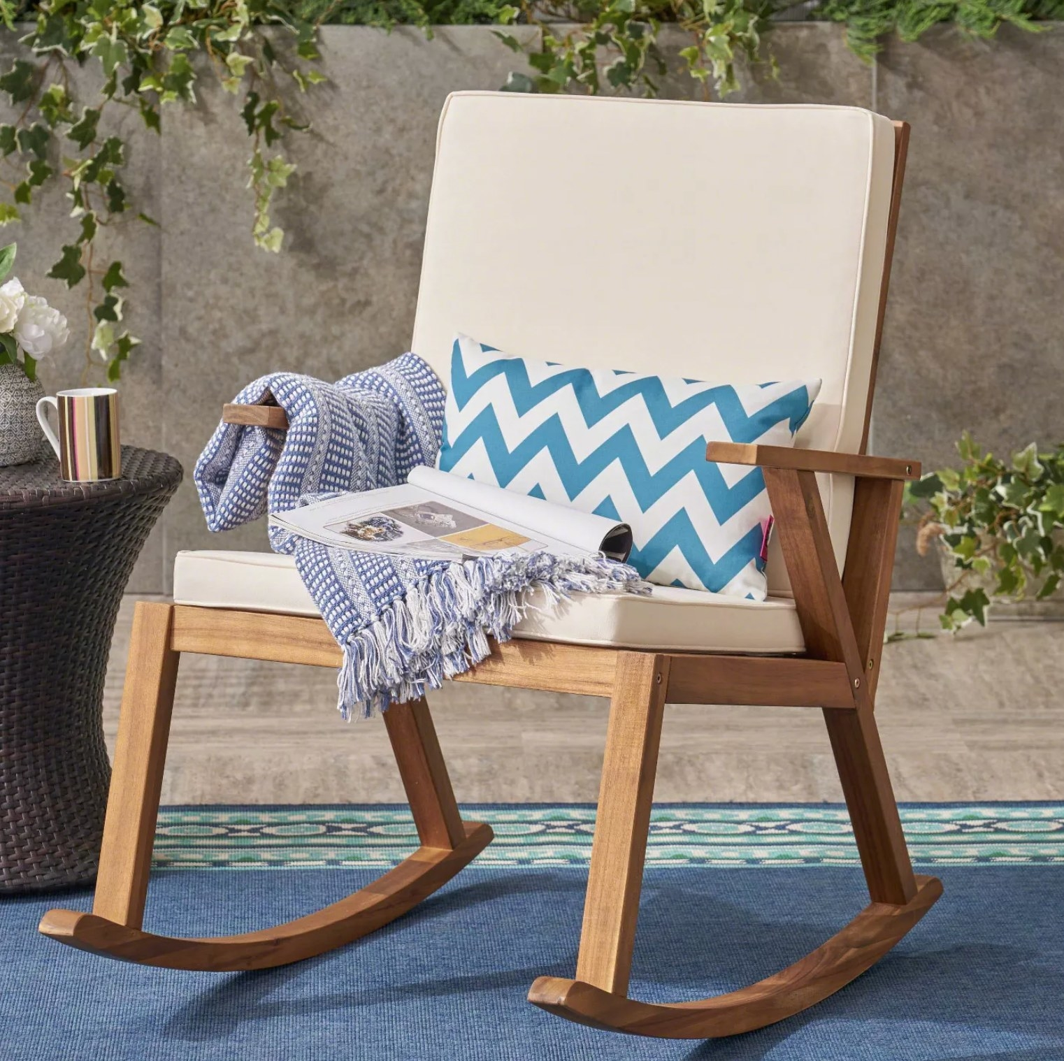 The teak chair styled with a pillow, blanket, and magazine