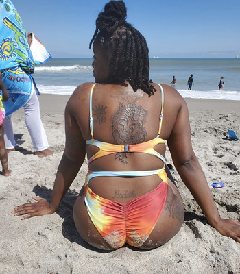 reviewer showing the back of the orange and blue swimsuit