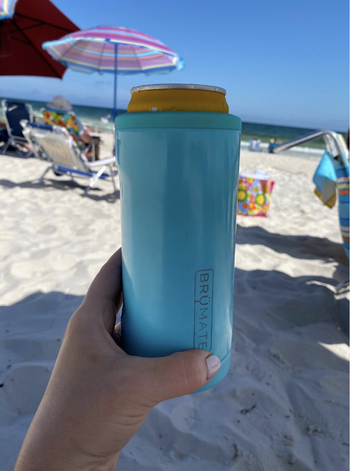 Reviewer holding up a blue insulated can cooler at the beach