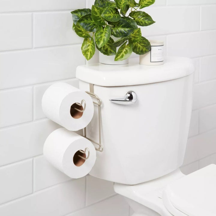 The holder sitting over a toilet with two rolls of toilet paper