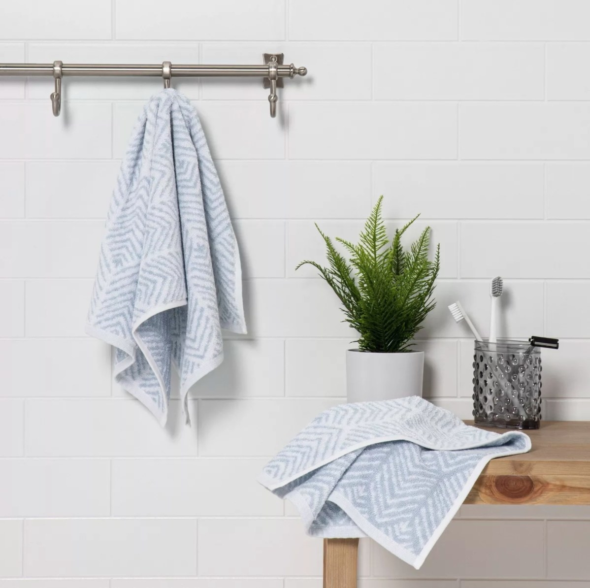 The two-pack of chevron hand towels in light blue in a bathroom