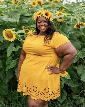 Reviewer in yellow version of the dress, which falls mid-thigh and cinches at waist