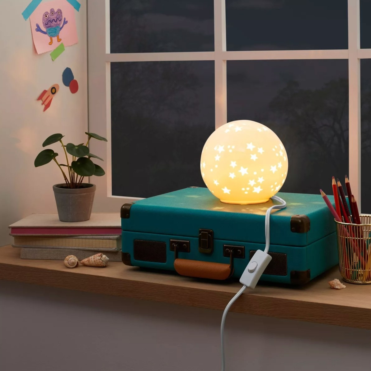 The starry globe nightlight glowing in a dark room next to a house plant