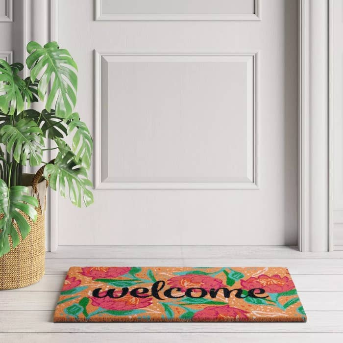 The 'welcome' doormat in black lettering with a floral background on a doorstep