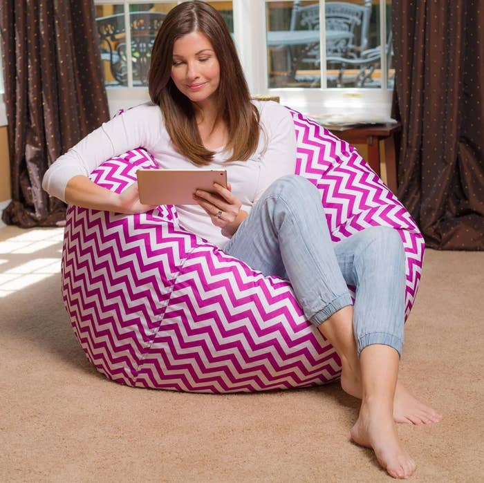 The bean bag in chevron purple/ white with a model playing on an iPad sitting in it