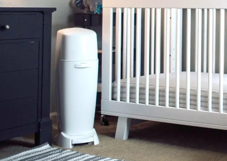 A diaper pail next to a crib and dresser