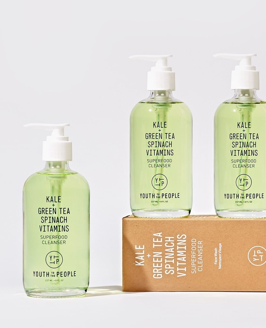 A trio of facial cleansers in transparent glass bottles arranged on a simple background