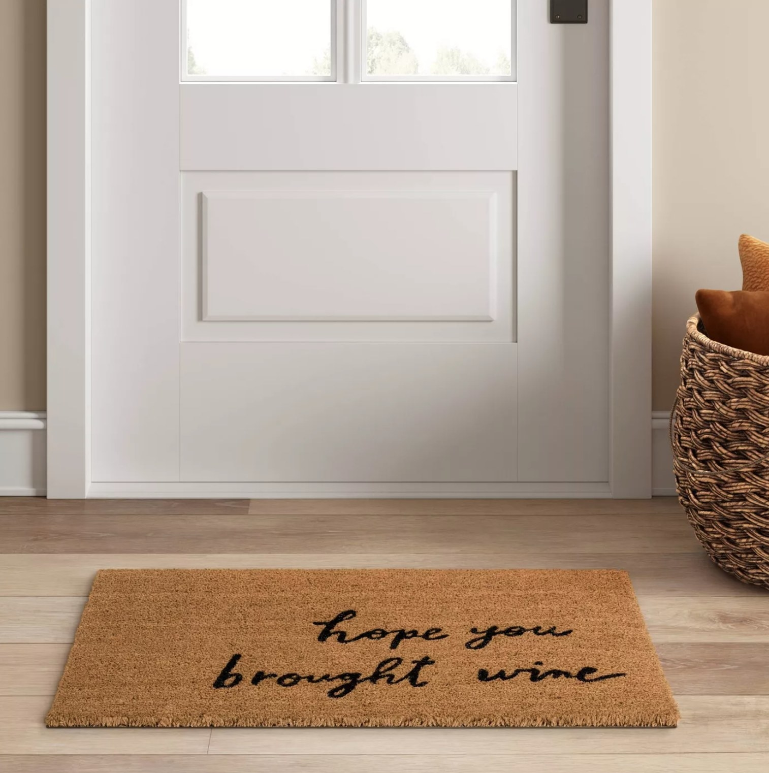 """The mat that says """"hope you brought wine"""" in front of a door"""