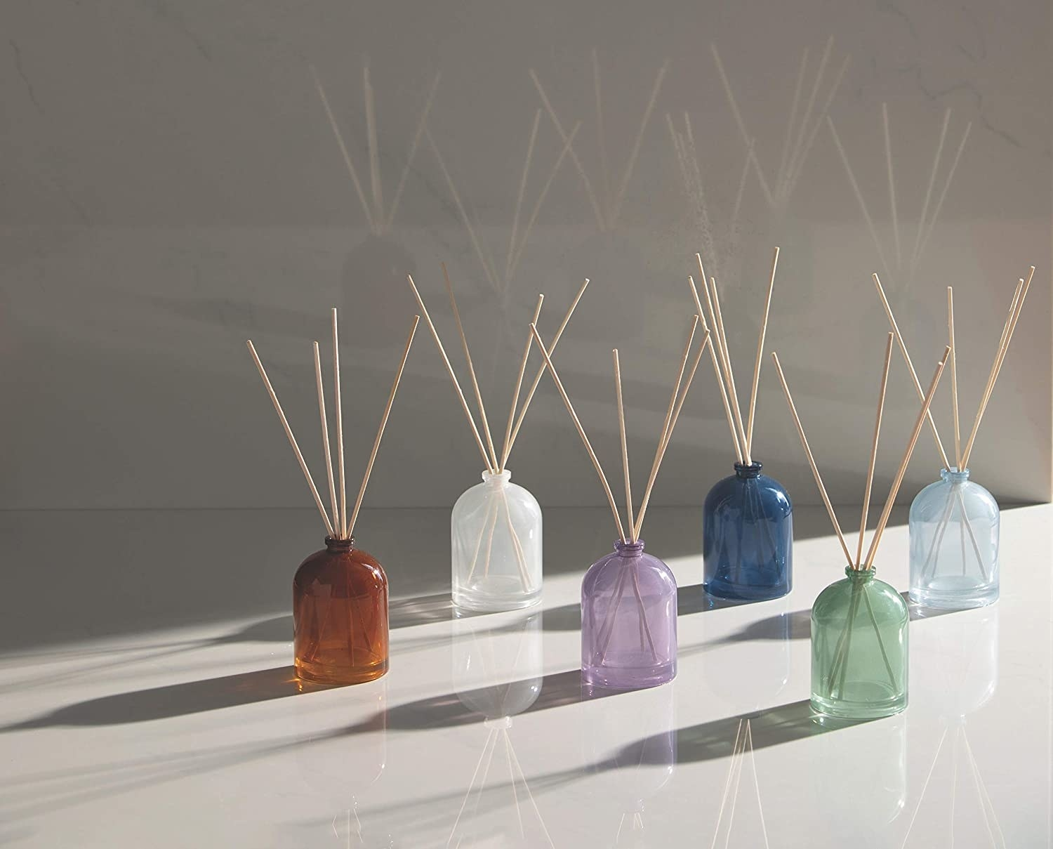 Six small glass bottles with fragrance sticks inside each