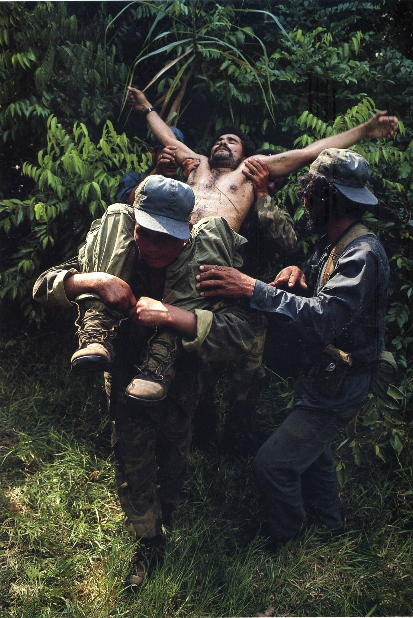 A dead or injured man is carried out of a jungle setting by soldiers with his arms extended, looking like Christ on the cross
