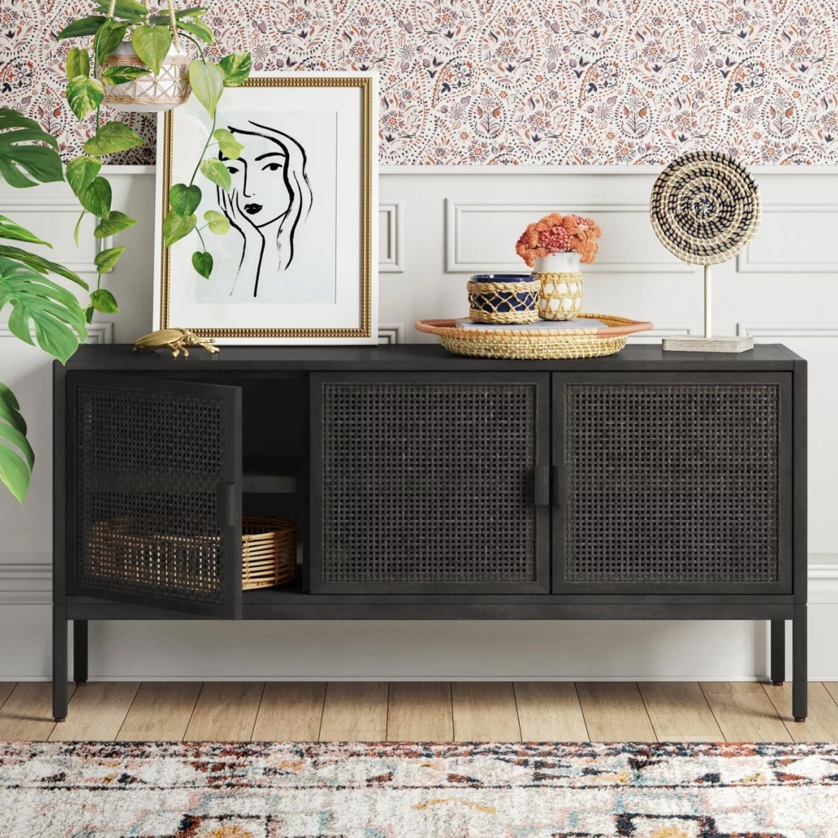 The rattan TV stand in black holding a framed drawing and a wicker basket