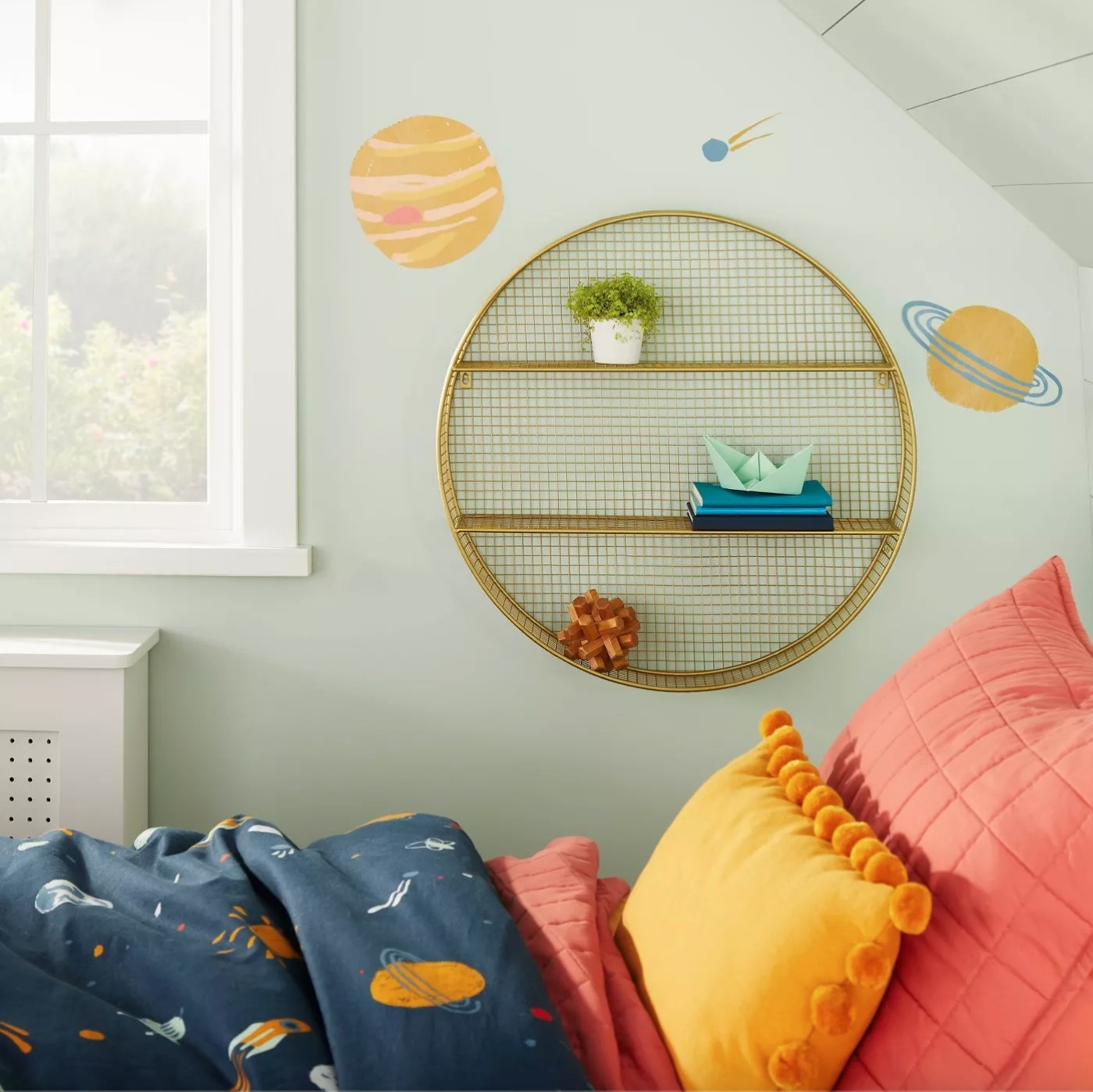 The metal circle shelf in gold holding a small plant and notebooks