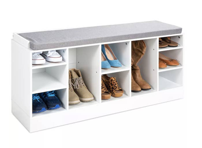 A white bench with a grey foam cushion atop and 10 compartments below to store shoes and boots
