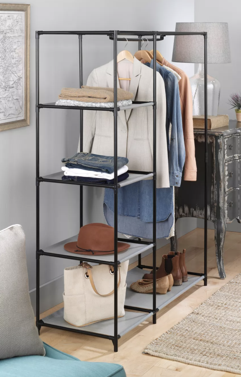 A freestanding closet wardrobe with 5 mesh shelves and a metal garment rod