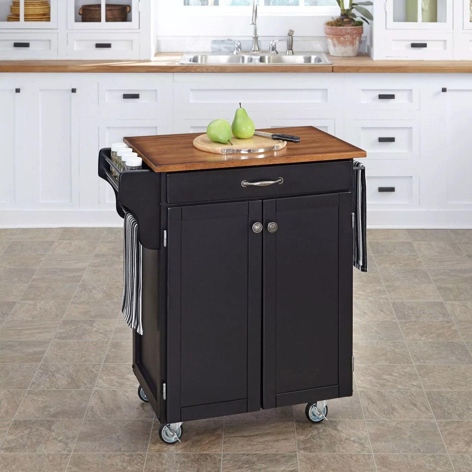 The cart in oak brown holding a cutting board and spices