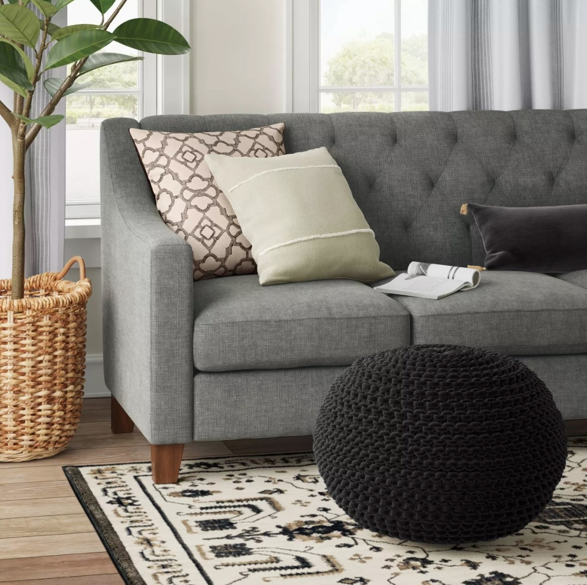 The chunky knit pouf in black sitting in front of a gray tufted sofa